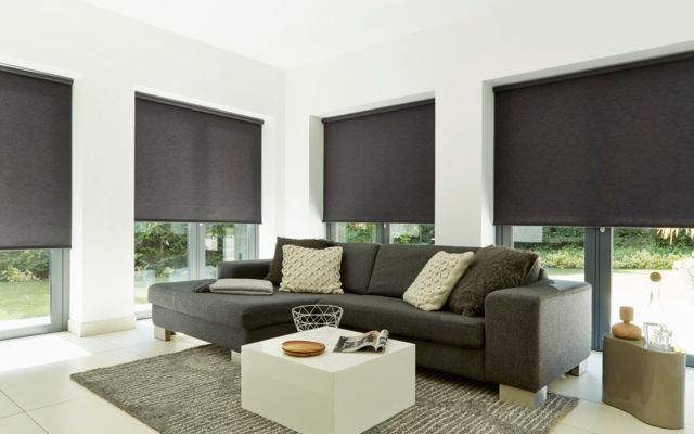 dark grey roller blinds in a modern living room window