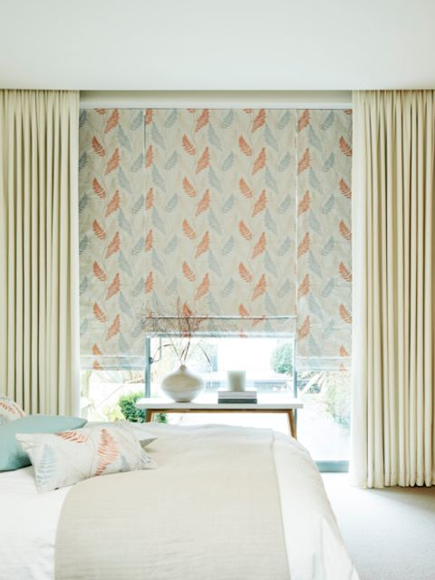 Florally decorated roller blinds fitted to large rectangular windows and are matched with cream coloured curtains in a bedroom that is decorated in neutral colours