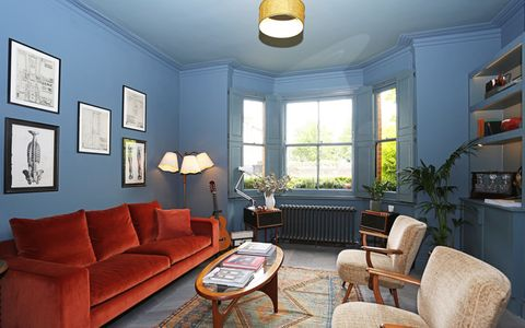 Large blue living room with an orange couch and custom colour solid tier on tier shutters on the bay window