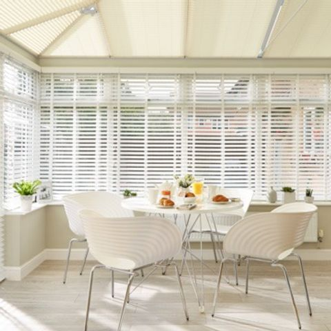 Conservatory with white wooden Venetian blinds and perfect fit roof blinds