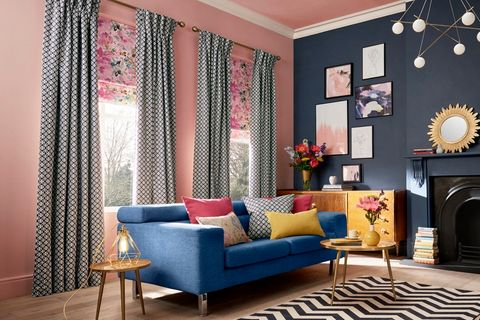 Grey curtains fitted with pink and blue florally patterned roman blinds in a living room decorated with pink and navy blue walls