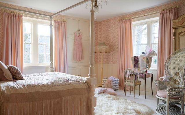 Large bedroom with a 4 poster bed and curtains in pink Clarence Chemise fabric
