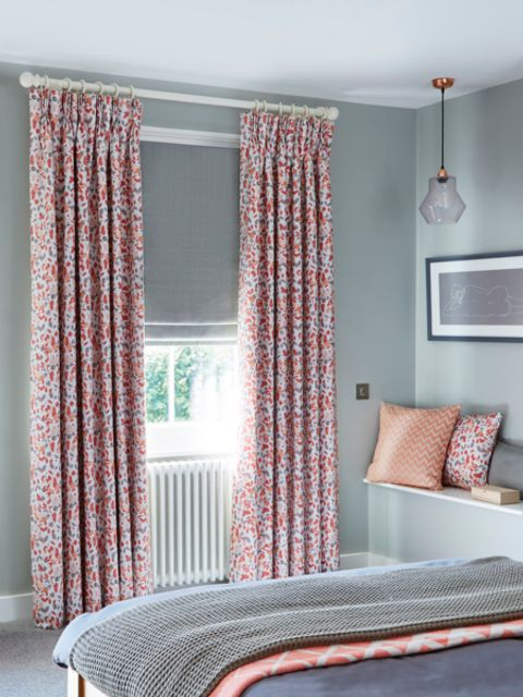 bright flowery curtains with light green roman blinds in a bedroom window