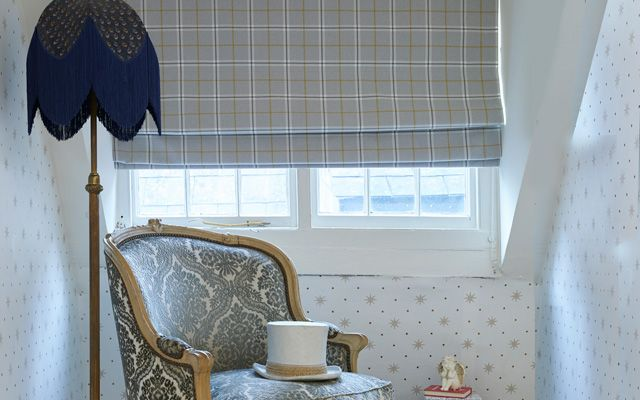 A large wing back chair in front of a small window which has a Roman blind in Wilcox Chartreuse fabric fitted to it