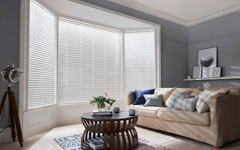 White coloured faux wood blinds fitted to a large bay shaped window in a living room decorated in grey and also features a sofa and coffee table