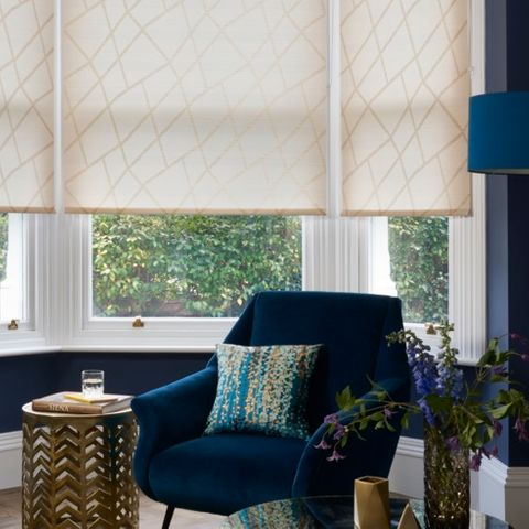 A blue chair placed in front of a bay window which is fitted with Roller blinds in Zimmer Gold fabric