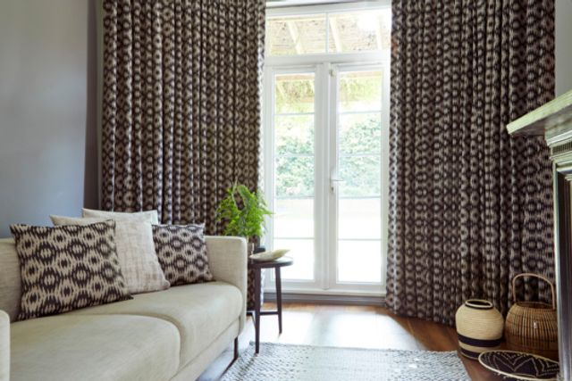 Black and cream diamond shaped print on curtains hanging on windows and cushions on sofa in a living room