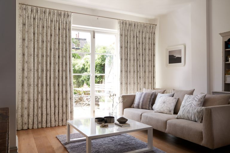 Cosy Neutral Living Room with floor to ceiling window dressed with Grey Pinch Pleat Curtains in Lavida Grey Fabric