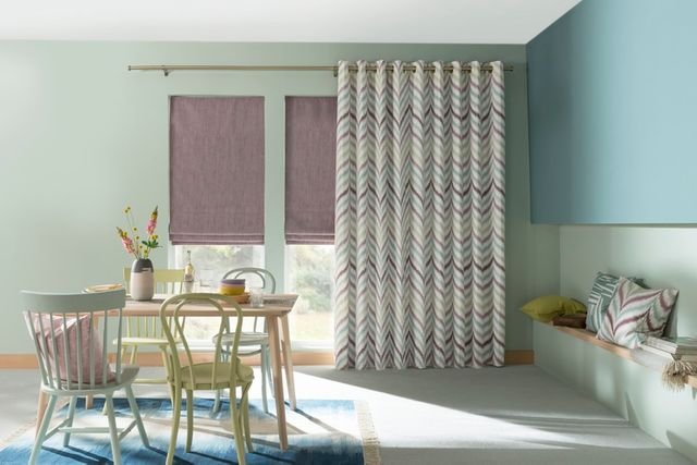 Purple roman blinds fitted to rectangular windows and matched with striped curtains in a dining room decorated with green and blue walls
