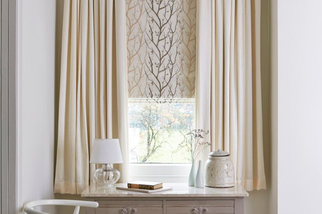 Cream curtains matched with cream and leaf patterned roman blinds in a study decorated in white