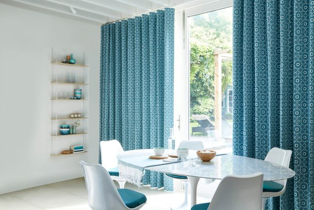 Dining area with patio doors with patterned kitchen curtains in blue fabric