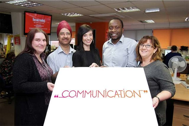 Five people gathered in an office space holding a sign which reads communication