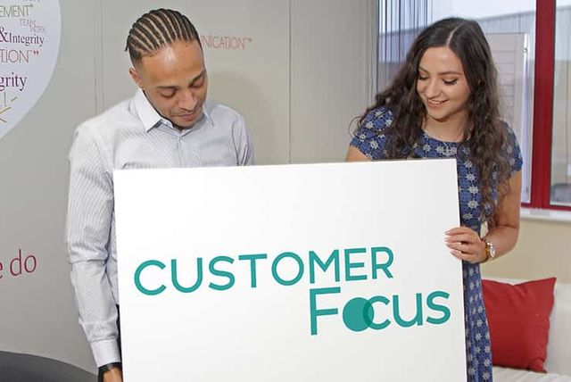 Two people posing for a sign that reads customer focus