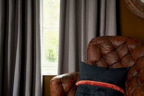 Close up detail of leather armchair in front of single window dressed with curtains