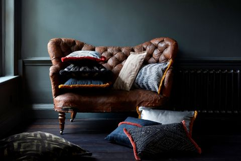 Cushions part of the Abigail Ahern collection of fabrics surround a brown leather chair in a rustic home