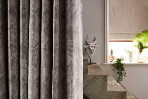Concrete staircase covered by Grey Pattern Curtains in Asaro Mink fabric and a window with Lucien Dust Cream Roman Blind with Colette Amour Orange Fringing