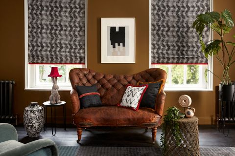 Edgy living room with brown leather sofa and two windows dressed with grey pattern roman blinds