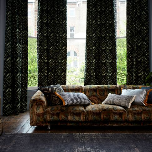 Edgy living room with dark decor and black and green velvet curtains from the Abigail Ahern collection