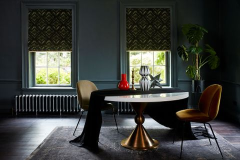 Modern gothic dining room with dark green patterned roman blinds by Abigail Ahern