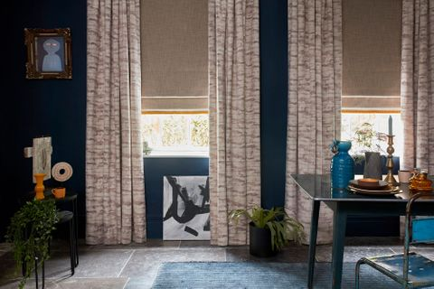 Cream coloured curtains paired with brown roman blinds both are fitted to rectangular windows in a dining room decorated in blue