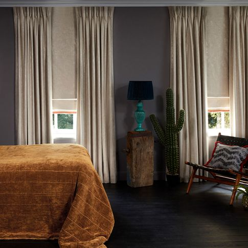 Bedroom with edgy decor and neutral Curtains in Abigail Ahern Lucien Dust fabric layered with Lucien Dust Roman Blind with a Colette Amour Orange Fringing