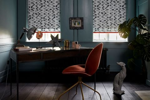 Dark home office with edgy decor and white pattern roman blinds