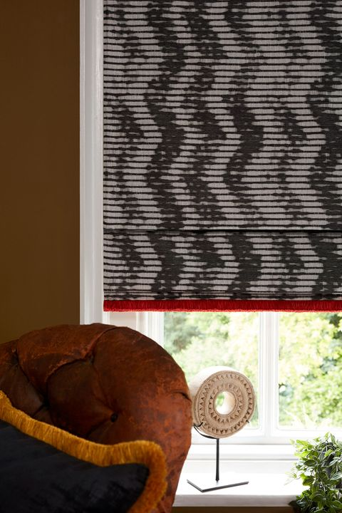 Close up of pattern roman blinds with red contrast fringing