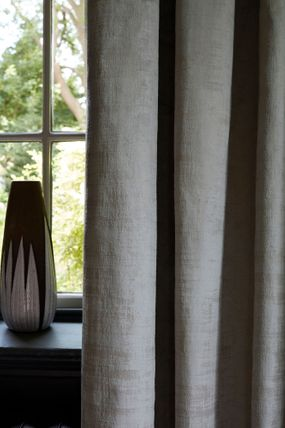 Close up detail of grey textured velvet curtains and black and white vase