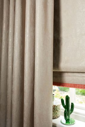 Cream roller blinds paired with cream curtains fitted to a rectangular shaped window