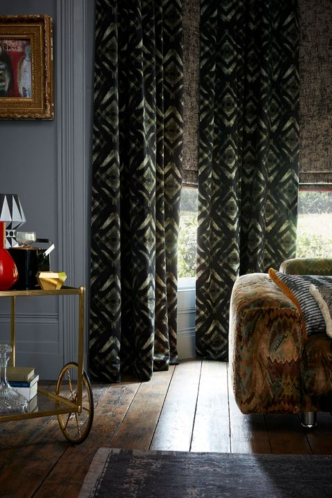 roman blinds matched with gasoline patterned curtains which are fitted to a bay window in a living room