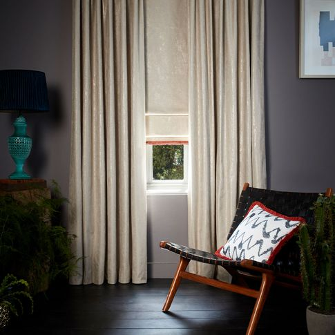Dark and moody room decorated with Abigail Ahern Lucien Dust Curtains and matching Roman Blinds with a Colette Amour Fringing and a pattern Cushion in Wolfe Smoulder fabric