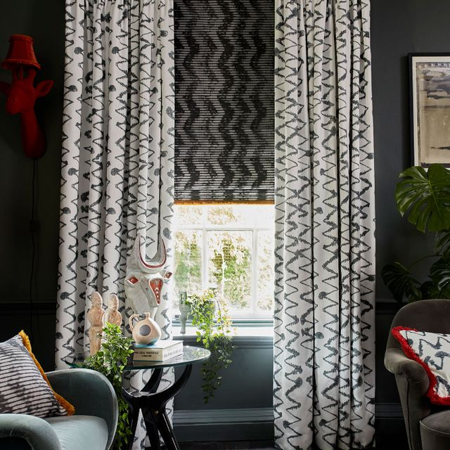 Dark and Eccentric Living Room decorated with White pattern curtains in Wolfe Smoulder fabric layered with a dark pattern roman blind in Cadillac noir fabric with a Colette Soleil fringing