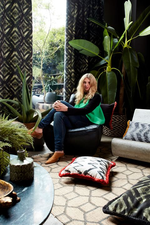 Abigail Ahern sat in a living room decorated with a range of plants and geometrically styled cushions, rug and curtains in black and white