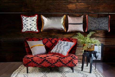 a series of rectangular and square shaped cushions in a different colours and styles from the abigail ahern collection are on a wall and some on a red and black styled sofa