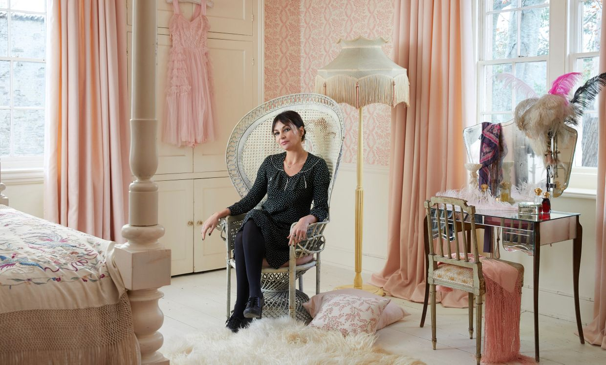 Pearle Lowe sitting on a chair in a lavishly decorated pink dressing room