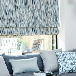A large window fitted with a Roman blind in Impression Marine with a blue couch in front of it