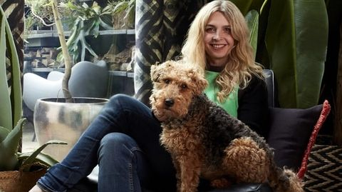 Abigail Ahern sat in a living decorated with geometrically styled curtains, plants and a dog sitting with her