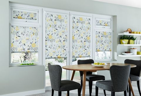 Dining room with french doors dressed with floral perfect fit blinds in mustard colour