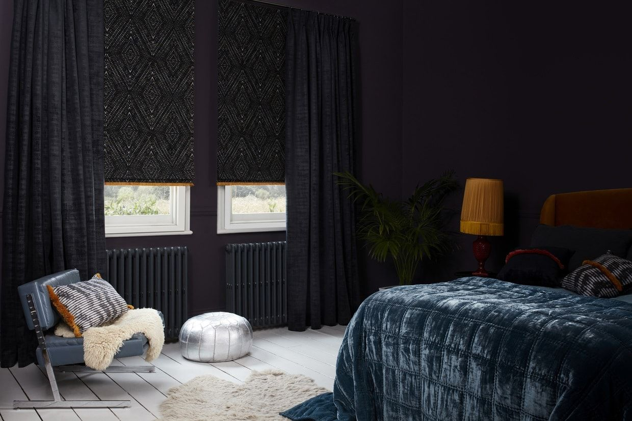 Black roman blinds matched with purple curtains in a bedroom with dark and light tones