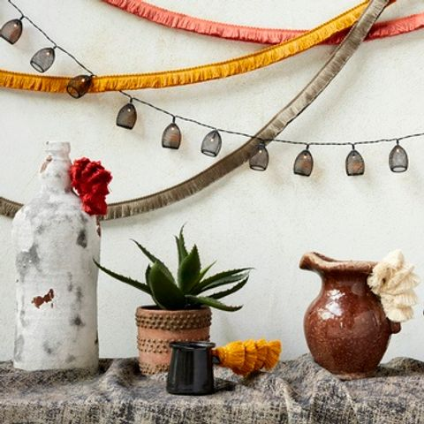 Grey Garcia Phantom fabric draped over a table that has jugs and plant pots on it