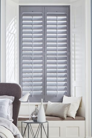 Grey wooden window shutters in a bedroom window