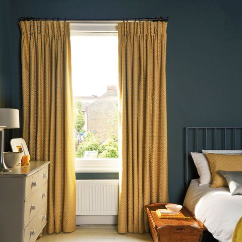 Yellow curtains fitted to a rectangular shaped window in a bedroom decorated in yellow and dark blue