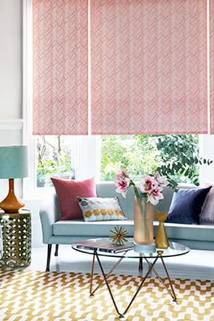 A pink Roller blind, in the Siesta Salmon design, covering a large bay window in a contemporary living room.