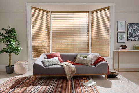 Bright living room with a bay window dressed with faux wooden blinds
