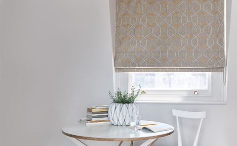 Minimalist room with small table and roman blinds in gold pattern fabric