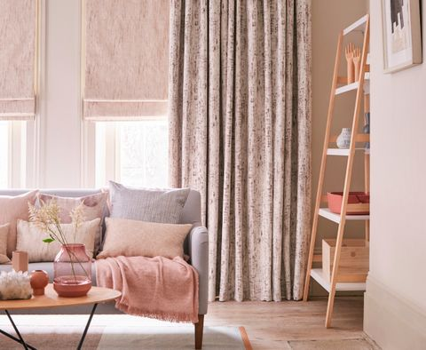 Pink velvet curtains with soft pink Roman blinds in a stylish living room with pastel decor