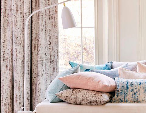 Cushions in pastel blue and pink velvet fabrics in front of a bay window hung with matching pink velvet curtains
