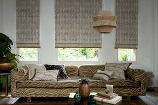 Large couch in front of a bay window with Asaro Mink Roman blinds with Colette Soleil fringing on the windows