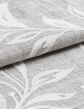 Light grey fabric with a leaf pattern in white that continously repeats