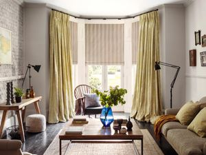A living room with Oralia Ochre Curtains and Howard Natural Roman blinds
